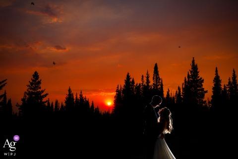 Foto artística de casamento no topo da montanha do Colorado mostrando A névoa de fumaça de um incêndio florestal local criado para alguns céus coloridos