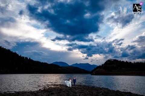 Foto artística do casamento do casal no Colorado, parando no lago antes de se juntar aos convidados na recepção