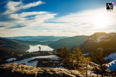 Foto artística do casamento de Donner Lake, Califórnia, da noiva e do noivo em uma montanha após a cerimônia de fuga ao nascer do sol no inverno
