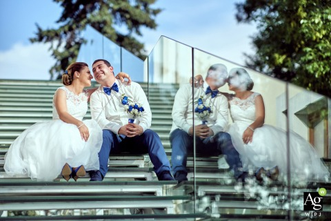 Museum of Contemporary Art, Sofia, Bulgaria couple posing for a wedding picture on the steps with glass reflections