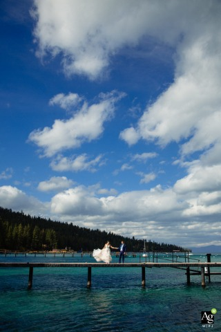 Lake Tahoe, CA wedding bride and groom dance on a private waterfront pier during an outdoor portrait session under the clouds