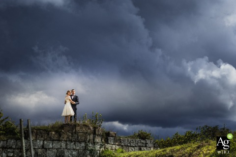 Jura bride and groom posing during a portrait session standing on a stone wall in the countryside under dark clouds