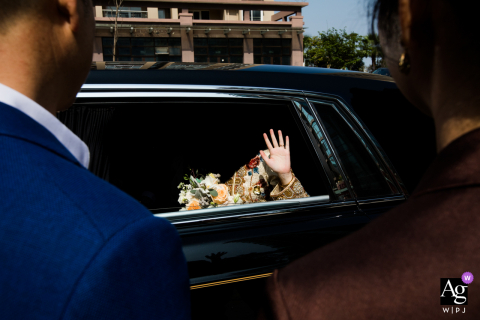Artistic wedding image from Zhejiang of the bride waving goodbye to her parents from the back of a car