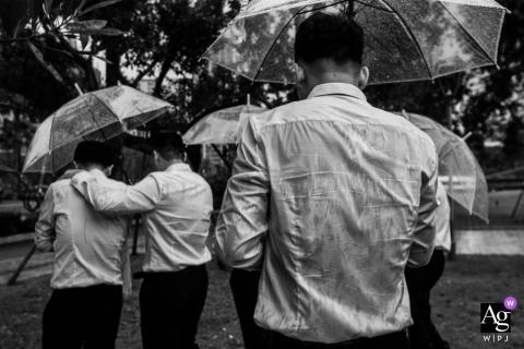 Foto de boda artística de Zhejiang del hotel de hombres que se refugian de la lluvia bajo sombrillas transparentes
