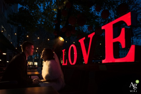 Sofia, Bulgaria couple posing for a wedding Night portrait with a giant lit sign reading, LOVE
