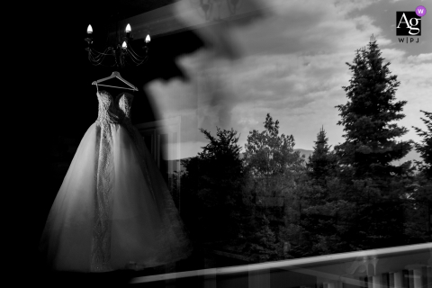 St. Sofia Golf Club artistic wedding photo of the wedding dress hanging by reflective glass windows