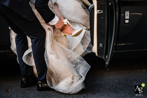 The groom helps the bride with her shoe in this creative wedding detail photo from Vrana Palace, Sofia, Bulgaria