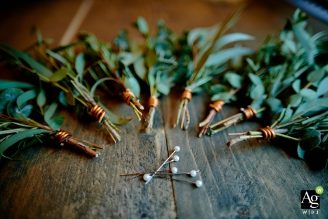 England wedding detail image of 	Buttonhole flowers and pins lying on distressed wood planks