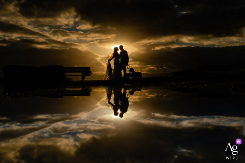 Foto artística de casamento em Thurstaston, Wirral, Inglaterra com um casal, uma silhueta do pôr do sol e reflexo