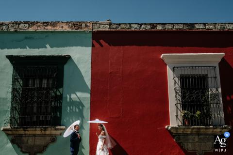 Fotografia artística de casamento de noivos na cidade de Oaxaca no dia do casamento em uma rua clássica e colorida de Oaxaca
