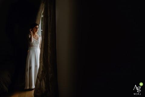 Bruidegom in de Auvergne-Rhône-Alpes poseren voor een portret naast een raamopening met natuurlijk licht