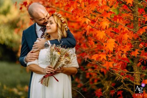 De huwelijksfotograaf van Auvergne-Rhône-Alpes legde dit artistieke huwelijksportret vast van de bruid en bruidegom met herfstbladeren