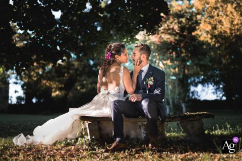 Retrato do dia do casamento de Andiran, França, da noiva e do noivo sentados em um banco de parque