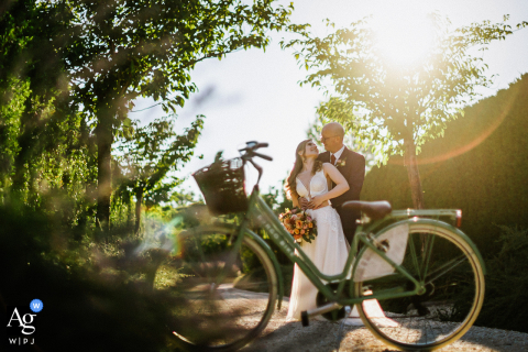 Siena wedding photographer captured this couple in a portrait with a  bike at sunset in the Borgo
