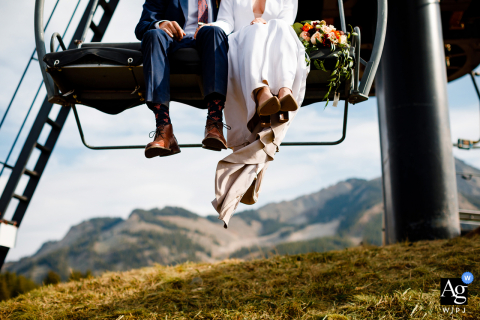Colorado wedding photographer captures this detail of a dirty mountain wedding dress of the bride while her and the groom take a ride on a ski lift