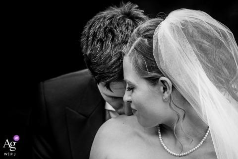 O fotógrafo de casamento do Reino Unido criou esta imagem com os noivos exibindo amor terno, noivo beijando os ombros da noiva em New Forest