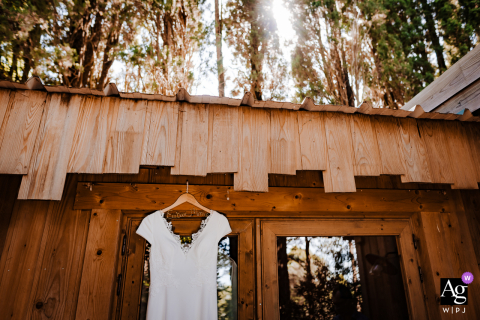 The Cabins in the Wood, France artistic wedding photo of the hanging dress outside in the sunshine