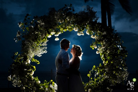 Southernmost Beach Resort bride and groom posing during a portrait session under a floral arch at night