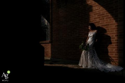 科瓦东加新娘摆在一张婚礼照在树荫下对着一束砖墙与她的鲜花