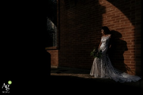 Covadonga bride posing for a wedding picture in the shade against a brick wall with her bouquet of flowers