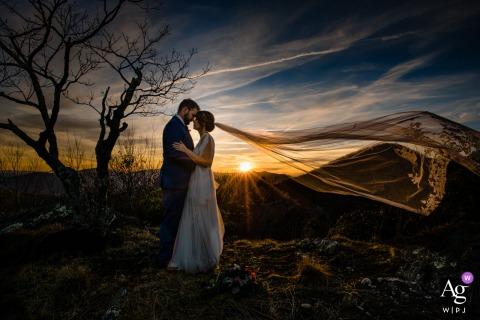 Jefferson, NC, retrato de casamento capturado pelo fotógrafo usando as linhas do cume e o vento, esperei pelo momento em que o véu da noiva assumisse a mesma forma das montanhas. O pôr do sol e o vento adicionaram um pouco de drama a esta imagem na Twickenham House