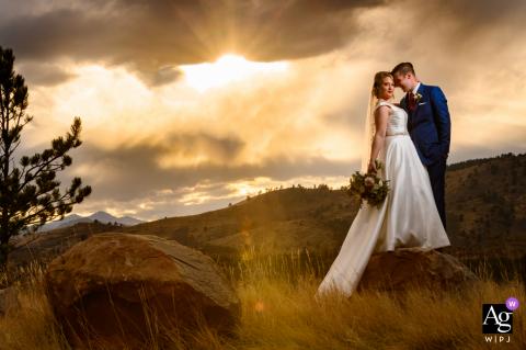 Foto artística do casamento em Fort Collins, CO, da noiva e do noivo compartilhando um minuto após a cerimônia no sopé da colina