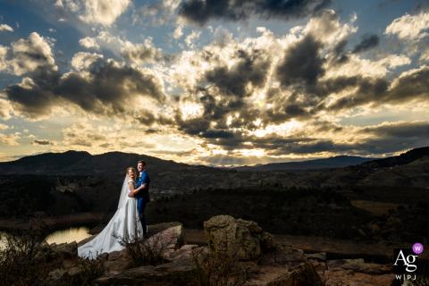 Foto artística de casamento em Fort Collins, CO criada após a cerimônia com a noiva escalando este cume em seus sapatos de salto alto e vestido de noiva para que pudéssemos capturar este lindo pôr do sol