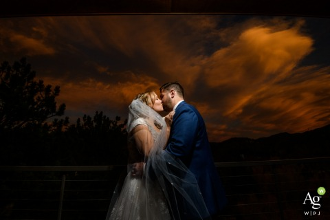 Skyview at Fall River, Estes Park, CO bride and groom posing during a portrait session as they share a kiss before dinner