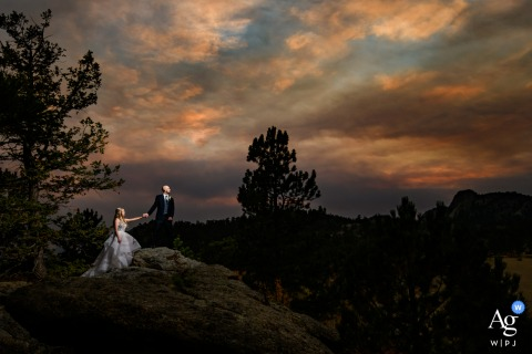 Estes Park, CO artistic wedding photo with A smoky sunset and the bride and groom as they scale to the top of a mountain ridge