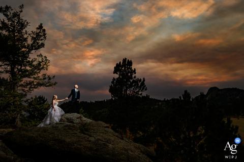 Foto artística de casamento em Estes Park, CO com Um pôr do sol esfumaçado e os noivos enquanto eles escalam até o topo de uma montanha