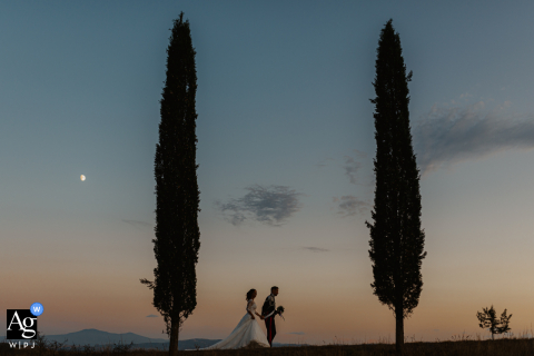 Siena wedding portrait of a bride and groom walking under the moon at their wedding reception in Tuscany