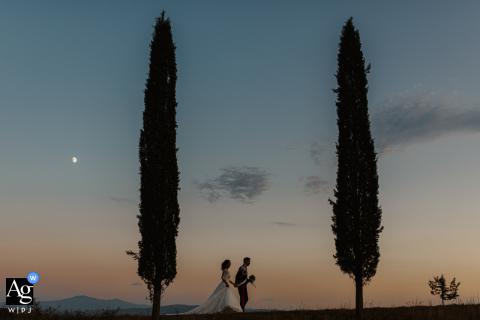 Retrato de casamento de uma noiva e um noivo caminhando sob a lua em Siena na recepção de casamento na Toscana