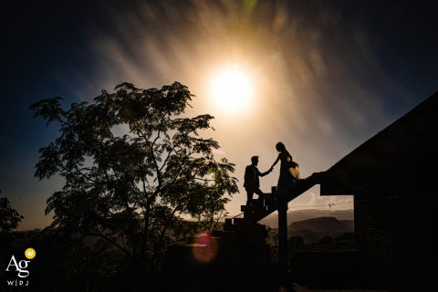 Artistic Istanbul wedding portrait in silhouette of a  ouple on high stairs, groom helping the bride to down stairs properly