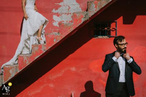 O fotógrafo de casamento em Istambul capturou uma noiva na escada e o noivo descendo as escadas em um fundo vermelho em Kadıköy