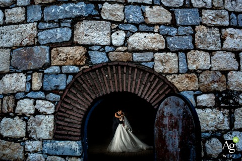 Izmir Karsiyaka Nikah Salonu, Turkey bride and groom posing during a portrait session in a brick arch under a stone wall