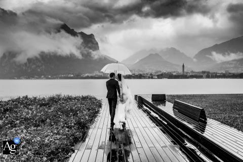 Foto artística do casamento de Lungolago di Lecco com o casal caminhando à beira do lago na chuva