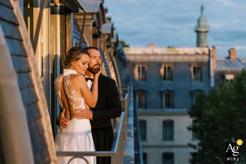 Künstlerisches Hochzeitsporträt des Hotels Ritz Paris von einem Paar auf dem Balkon in der niedrigen Sonne