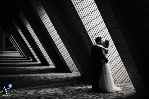 Hong Kong wedding portrait of a kissing bride and groom. The light and shadow, and the lines formed by the architecture makes the photo. Shot with available light at the Hong Cultural Centre