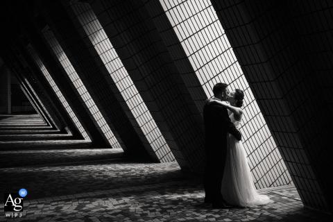 Retrato de casamento de Hong Kong de uma noiva e um noivo beijando. A luz e a sombra, e as linhas formadas pela arquitetura formam a foto. Filmado com luz disponível no Centro Cultural Hong