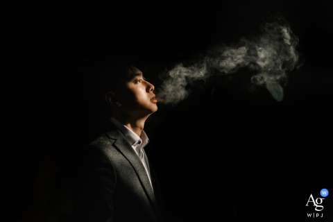 Fujian wedding image of the groom playing by blowing smoke into the darkened room with a splash of light