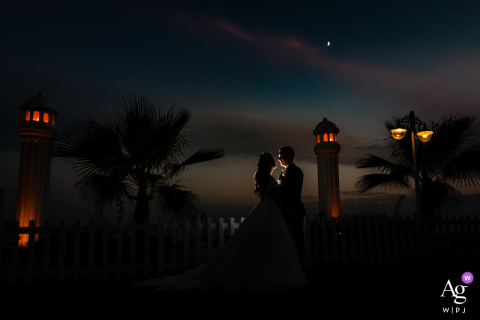 Kadıköy Artistic wedding portrait of the bride and groom posing in front of a lighthouse