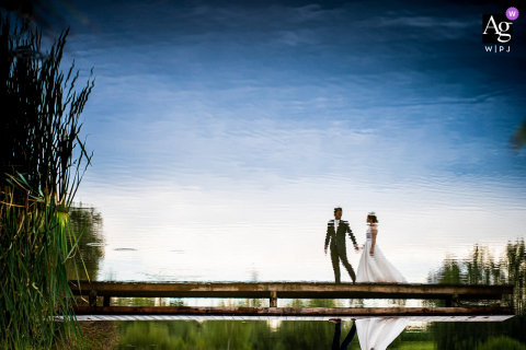 Hluboké wedding portrait of the bride and groom walking on the pier