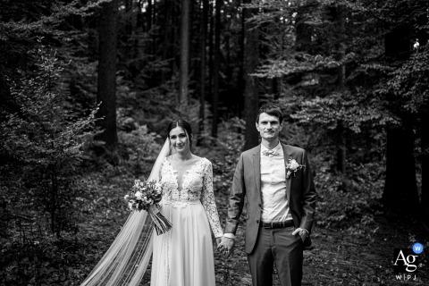 Retrato de boda artístico Valašská Polanka de una novia y el novio tomados de la mano en el bosque