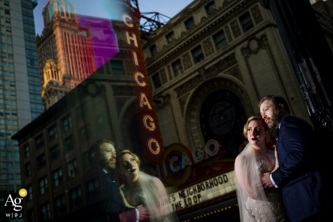 Artistic Reflected Chicago portrait of the bride and groom in front of the Chicago Theatre