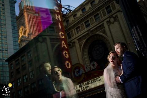 Retrato artístico refletido de Chicago da noiva e do noivo em frente ao Chicago Theatre