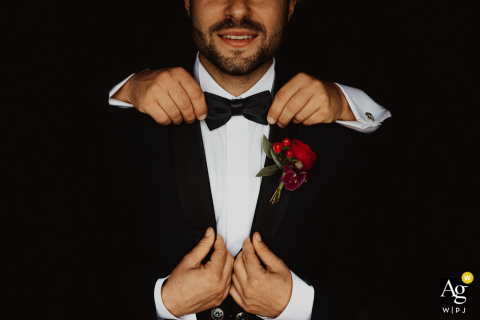 Artistic Rome image of the groom having help adjusting tie and suit at his at-home wedding preparations