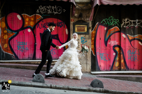 Istanbul wedding portrait of the bride and groom walking through the streets with a colorful graffiti background
