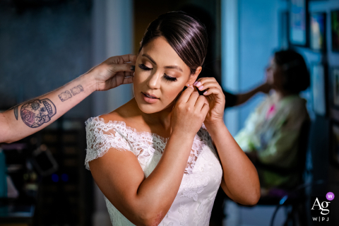 Chicago Bride puts on her earrings while her sister helps during this at-home wedding preparation photoshoot