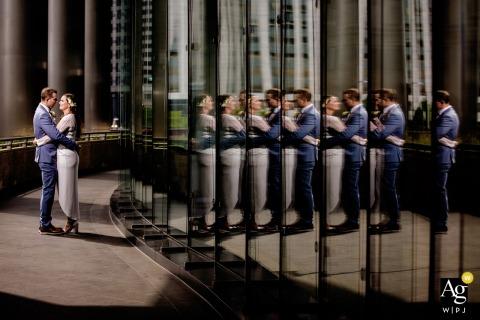 Retrato criativo da noiva e do noivo no centro de Chicago sendo refletido várias vezes em um edifício