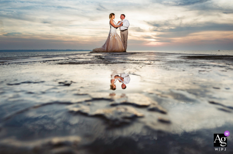 Portorož, Slovenia artistic wedding portrait of a couple standing at the pier at sunset with a reflection from the sea water